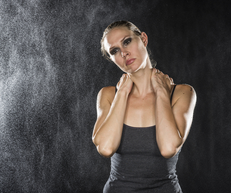 caucasian water drops: Half Body Shot of an Athletic Young Woman Holding her Neck While Looking Into the Distance with Pensive Facial Expression. Captured in Studio on a Black Background with Water Drops.