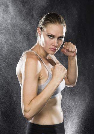 pugilist: Disparo medio cuerpo de un atl�tico de la mujer en Combate Pose de mirada feroz en la c�mara contra gotas de agua de fondo. Foto de archivo