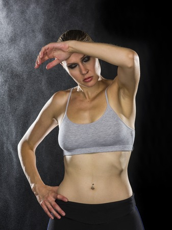 Half Body Shot of a Sporty Young Woman Wiping Sweat on her Forehead Using Hands After Workout Against Back Background with Water Drops Effect. Archivio Fotografico