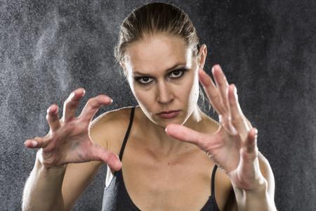 defensa personal: Close up Mujer joven atlética Alcanzar sus manos hacia la cámara con Fierce Expresión facial contra gotas de agua de fondo. Foto de archivo