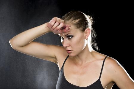 Close up premurosa Atletico giovane donna che esamina la distanza con la mano sulla sua fronte su sfondo nero con gocce d'acqua Effect. Archivio Fotografico - 45598263