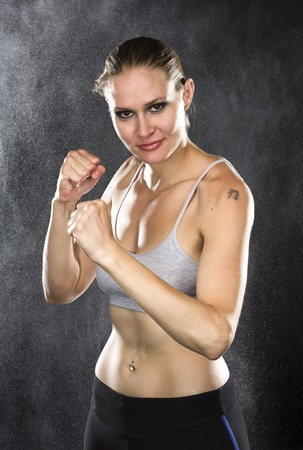 pugilist: Half Body Shot of a Young Fighter Woman in Combat Pose, Smiling at the Camera Against Water Drops Background Stock Photo