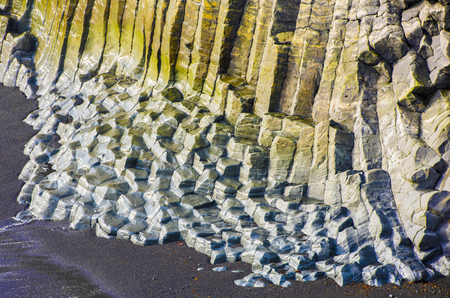 geological formation: Big basalt rocks with yellow and blue moss on the beach