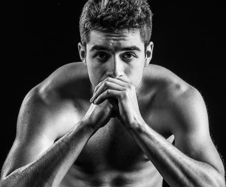 Shirtless muscular man staring into camera seriously