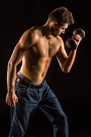 Young Man Lifting Dumbell to Exercise Biceps - Dumbbell Concentration Curl
