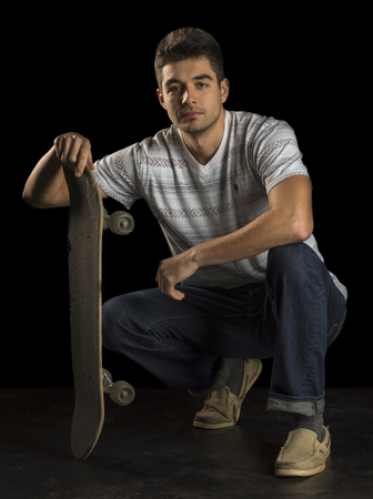 Portrait of a male skater holding a skateboard and looking at the camera