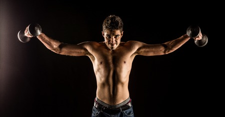 Man stretching arms outward doing a Standing Dumbbell Chest Fly. Studio composite over black.