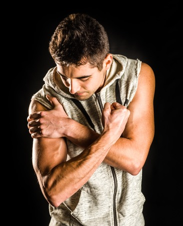 Young fit man flexing his bicep isolated on black background