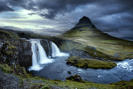 Cloudy overcast day of the Kirkjufellsfoss Waterfall with Kirkjufell mountain in the background in Iceland. Long exposure.