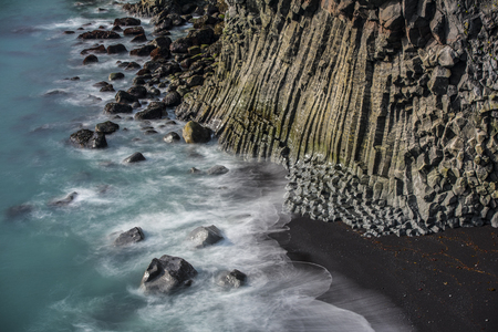 Ocean waves breaking on basalt rocks