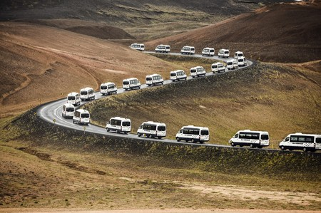 Tour bus vans on a curved road leading through a mountain landscape in Iceland.