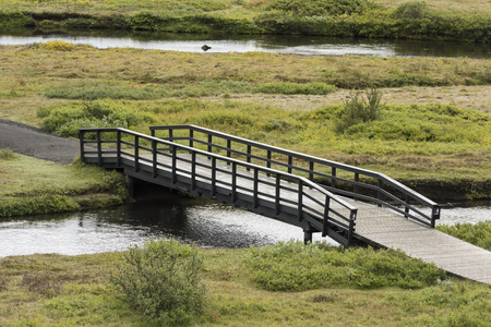 Long Narrow Walking Bridge in Iceland with rails on the edges crossing a river stream Reklamní fotografie