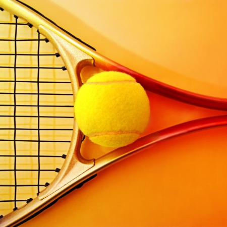 Tennis racket and ball on hot orange backround