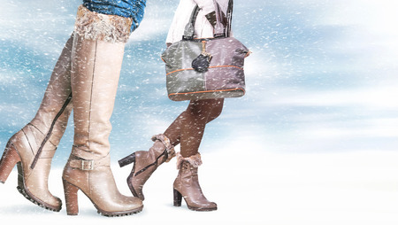 woman fur: Female feet in winter shoes, snowfall in the foreground
