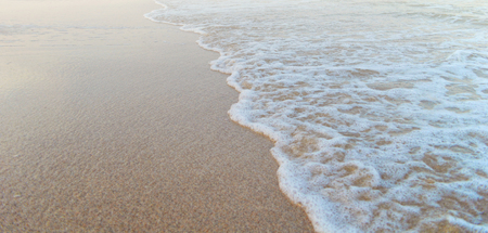 white water: Soft sea waves rolls on golden beach. Foam on sand created by sea waves Stock Photo