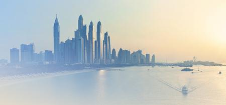 Dubai Marina skyline at sunset, United Arab Emirates. Silhouettes of Dubai skyscrapers illuminated by evening sunlight