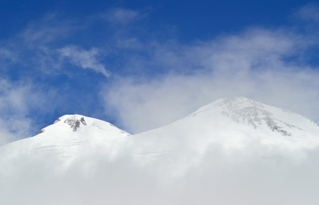 Peak of Elbrus mountain viewed through fog and clouds. Head of Elbrus mountain covered by ice and snow