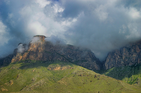 Mountain range and canyon surrounded by clouds. Dramatic clouds hang over the cliffs and meadows Stock Photo