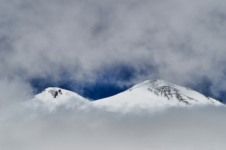 Peak of Elbrus mountain viewed through fog and clouds. Top of Elbrus mountain covered by ice and snow