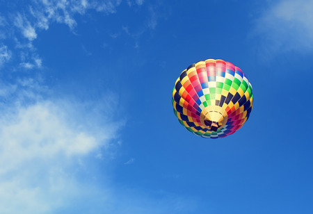 Colorful hot air balloon is rising up to the blue sky with clouds. Hot air balloon viewed from below.