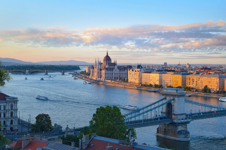 Panoramic sunset view of parliament building and chain bridge in Budapest, Hungary. Motor boats moving on Danube river in front of Hungarian parliament historical building.