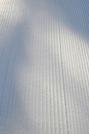Ski track prepared for cross-country skiing on a sunny winter day. Sparkling snow under the sunlight