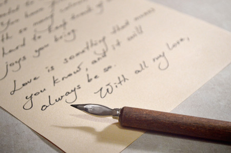 Close up view of love letter and vintage dip pen with wooden handle