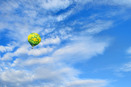 Yellow green hot air balloon is rising up to the blue sky with clouds. Hot air balloon on picturesque sky background