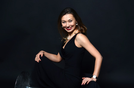 pearl jewelry: Smiling white woman with long brown and blond hair in white pearl jewelry in long black evening dress on dark background