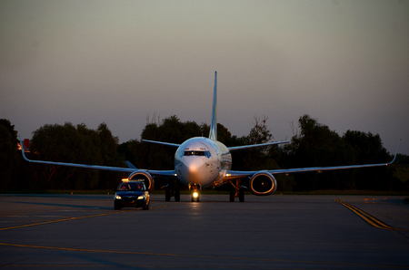 escorting: Aircraft escorting by airport support service on the sunset Editorial