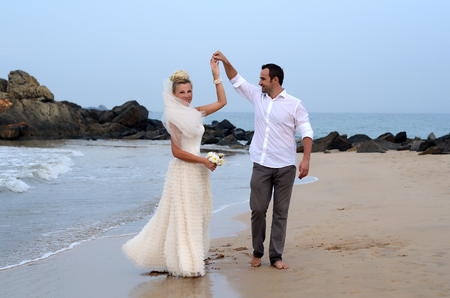 barefooted: Happy white newlyweds dancing on the seaside Stock Photo