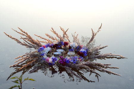 tell fortune: Wreath of flowers with burning candles on the water