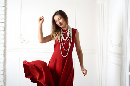 brown hair blue eyes: Smiling white woman with long brown and blond hair in white pearl jewelry in long red evening dress on light background