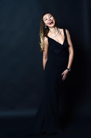 pearl jewelry: Laughing white woman with long brown and blond hair in white pearl jewelry in long black evening dress on dark background