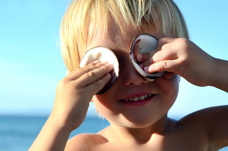 blonde boy: European blonde boy with shells Stock Photo