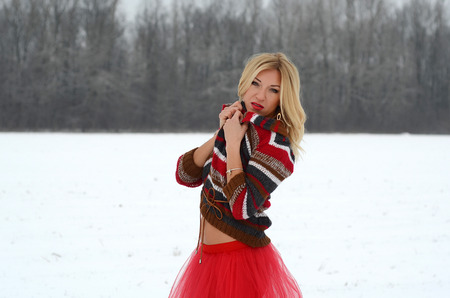 enchantress: beautiful white blond girl with blue eyes, long hair in the snow in a red dress with a red veil, red lipstick