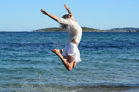 european bronzed white girl in the white clothes jumping on the sea