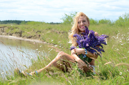 heir: beautiful white blond girl with long hair, blue eyes, wearing a white bikini with a big bouquet of purple flowers, sitting in a field with green grass and flowers on the bank of a lake