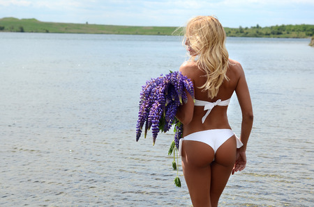 heir: beautiful white blond girl with long hair in white bikini with a big bouquet of purple flowers, standing in the water in a large lake Stock Photo