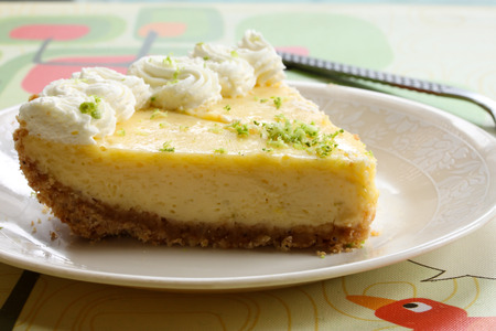 Slice of a key lime pie on white plate