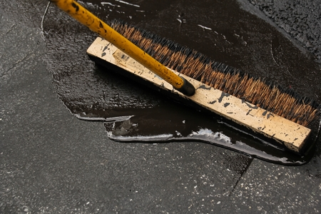 Sealing a damaged asphalt blcktop drive way with large brush Stock Photo