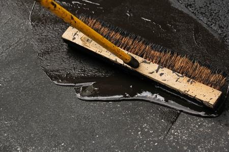 drive way: Sealing a damaged asphalt blcktop drive way with large brush Stock Photo