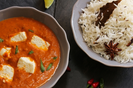 Paneer Butter masala and cooked rice Indian Curry vegetarian Dinner Stock Photo
