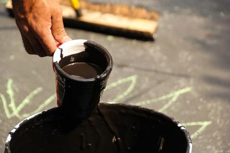 sealing: Sealing a damaged asphalt blcktop drive way with large brush Stock Photo