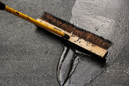 Sealing a damaged asphalt blcktop drive way with large brush Banque d'images