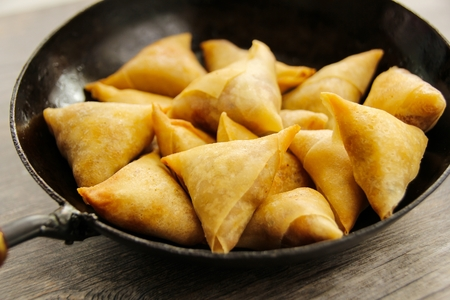 Samosas Indian snack fried food in a frying pan Banque d'images