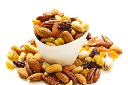 Mezcla surtido de frutas secas y nueces almendras, anacardos, cacahuetes, pasas y nueces en un tazón blanco