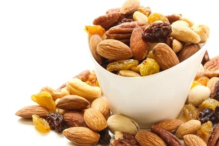 Geassorteerde mix van droge vruchten en noten amandel, cashew, pindakaas, rozijnen en walnoot in witte kom