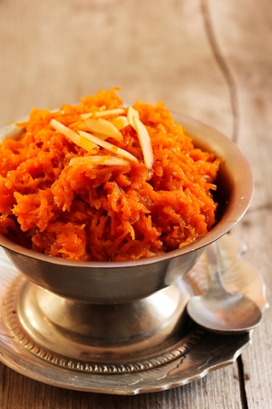 Carrot halwa - Diwali sweet made of carrots milk and sugar in rustic steel container