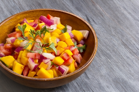 Homemade Mango salsa served in a wooden plate